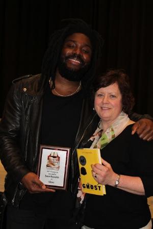 Christina Giving Jason Reynolds an Ohio Buckeye Childrens and Teen Book Award